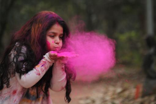 Free Stock Photo of Young Girl Blowing Pink Powder
