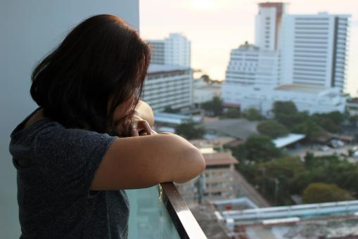 Free Stock Photo of Urban Lifestyle: An Asian  lady looks out at high-rise city buildings