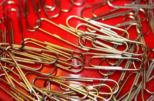 Free Stock Photo of Metallic paperclips on red background