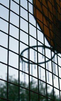 Free Stock Photo of A basketball hoop behind a metal lattice