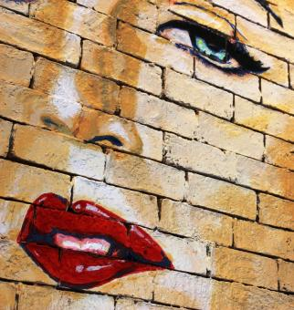 Free Stock Photo of Woman's face with red lips painted on a brick wall