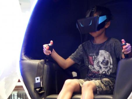 Free Stock Photo of Boy wearing virtual reality headset in game capsule