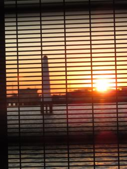 Free Stock Photo of A lighthouse and sunset behind window blinds