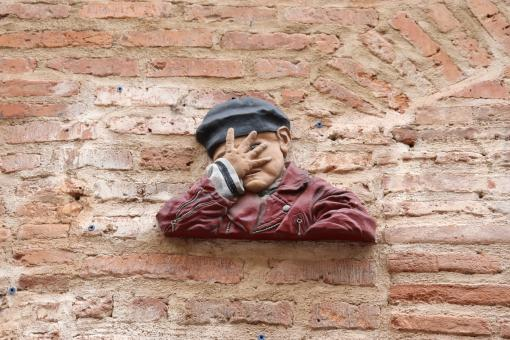 Free Stock Photo of Sculpture on a brick wall of a child hiding his face
