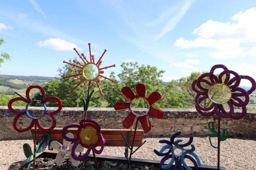 Free Stock Photo of Various iron colored flower sculptures in a street