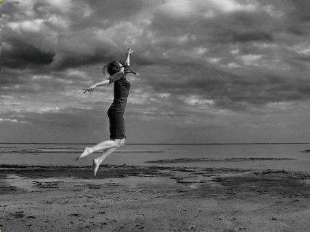 Free Stock Photo of Girl Jumping on the Beach - Black and White
