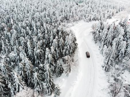 Free Stock Photo of Car Driving on a Snowy Road in The Woods