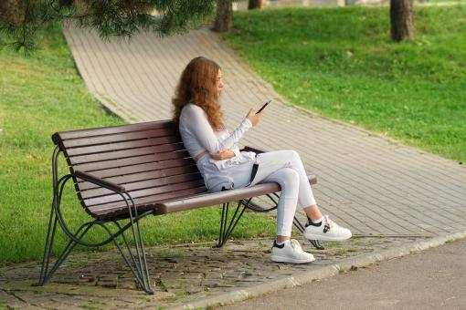 Free Stock Photo of Young girl sitting on bench with phone
