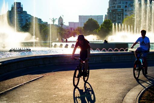Free Stock Photo of Bicyclist walking near fountains