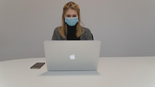 Free Stock Photo of Woman with Mask Behind Laptop