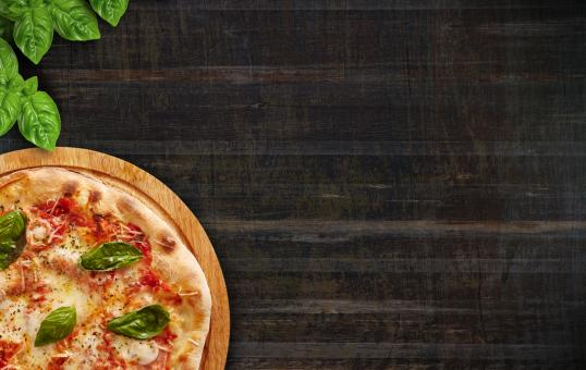 Free Stock Photo of Pizza and Basil Leaves on Wood Background - With Copyspace