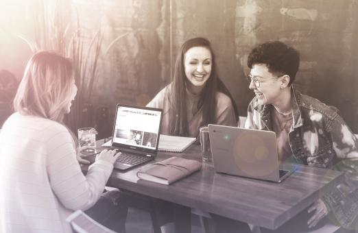 Free Stock Photo of Friends Smiling and Working with Laptops at a Cafe