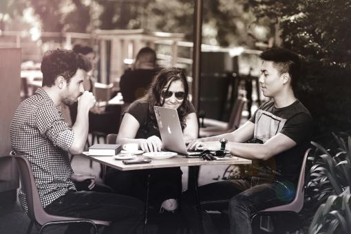 Free Stock Photo of Friends Smiling and Working with Laptops at a Cafe Terrace
