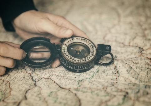 Free Stock Photo of Person Holding Compass Over Map - The Path Forward