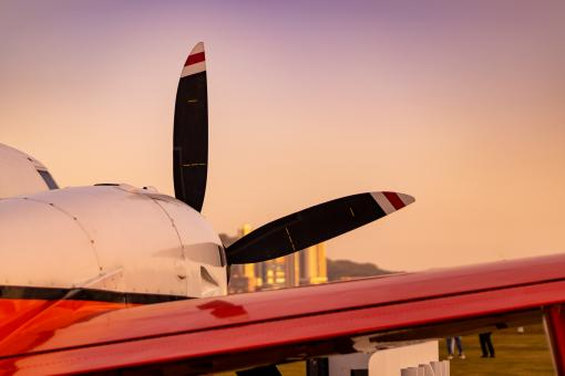 Free Stock Photo of Propeller Plane Parking on green grass in a sunset city background