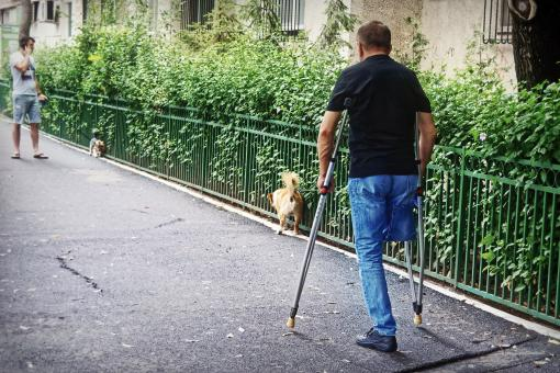 Free Stock Photo of Man with a disability walking the dog on the street