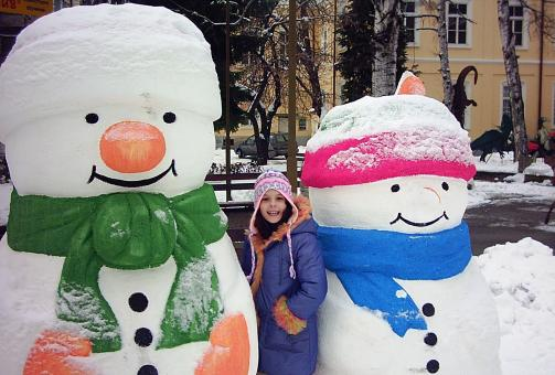Snowmen and a girl - Free Stock Photo