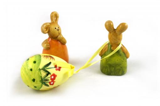 Easter rabbits - one dragging an egg - Free Stock Photo