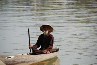 Vietnamese man on a boat Free Photo