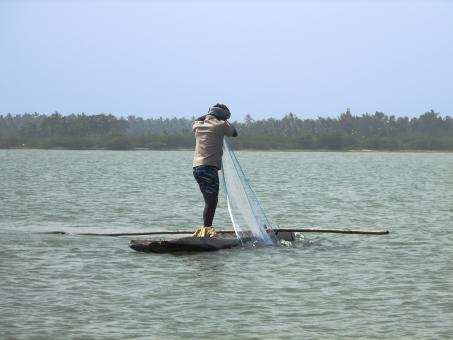 Fisherman in a log boat - Free Stock Photo
