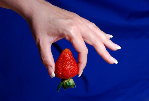 Holding a strawberry - Free Stock Photo