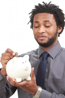 Man putting money into a piggy bank - Free Stock Photo
