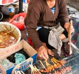 Free Photo - Asian woman selling sate on the street