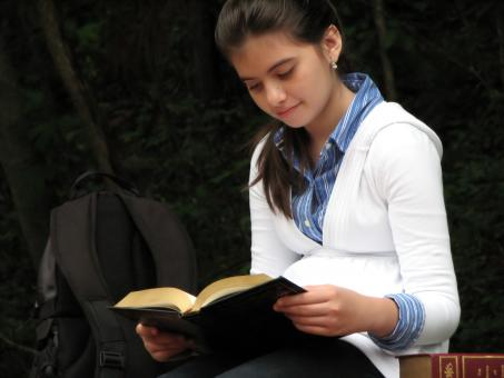 A young schoolgirl reading a book - Free Stock Photo
