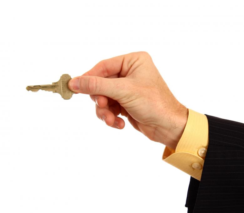A hand in a business suit holding a key Free Photo