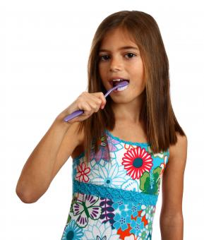 A pretty young girl brushing her teeth - Free Stock Photo