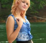 Free Photo - A beautiful young woman posing by a lake