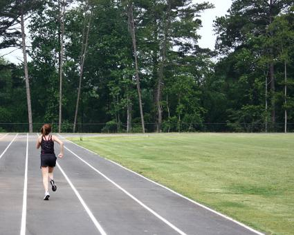A cute young girl on a track field - Free Stock Photo