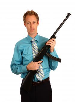 A young businessman holding a rifle - Free Stock Photo