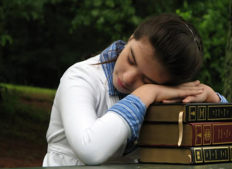 Free Stock Photo of Schoolgirl resting her head on books Created by Benjamin Miller