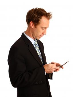 A businessman texting on a cell phone - Free Stock Photo
