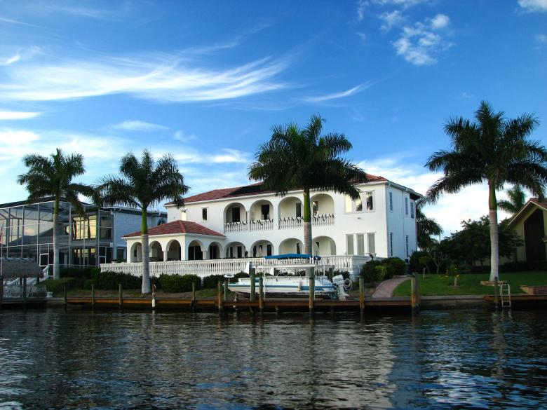 Free Stock Photo of A fancy house along the water with palms Created by Benjamin Miller