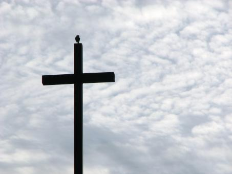 A cross before a cloudy sunset sky - Free Stock Photo