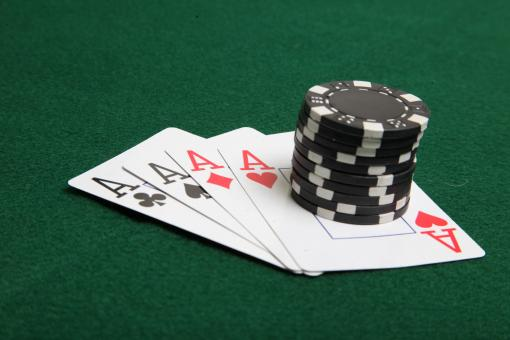 Stack of black poker chips on four aces. - Free Stock Photo
