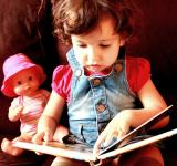 Free Photo - Child reading a book with doll
