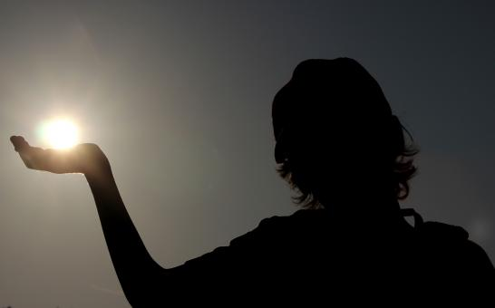 Silhouette of a child holding the sun - Free Stock Photo