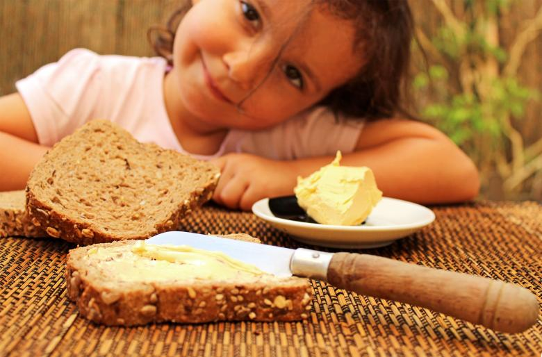 Free Stock Photo of Child preparing to eat bread and butter Created by Jack Moreh