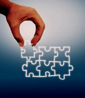 Hand assembling jigsaw on virtual screen - Free Stock Photo