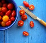 Free Photo -  Freshly sliced organic cherry tomatoes on blue wooden background