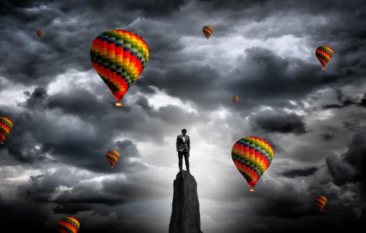 Businessman on the summit surrounded by hot air balloons - Free Stock Photo