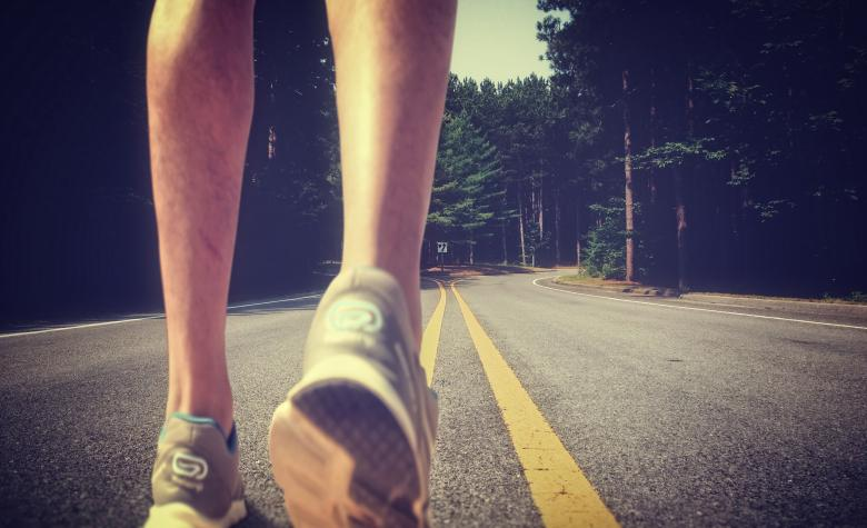 Feet of an athlete running on a deserted road Free Photo
