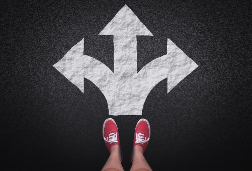 At a crossroads - Decisions and choices concept with large arrow signs - Free Stock Photo