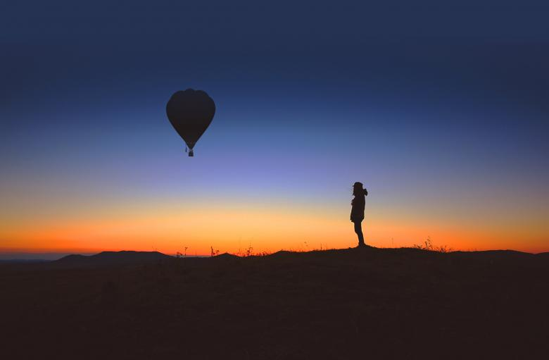 Free Stock Photo of Alone person observes an hot air balloon at sunrise Created by Jack Moreh