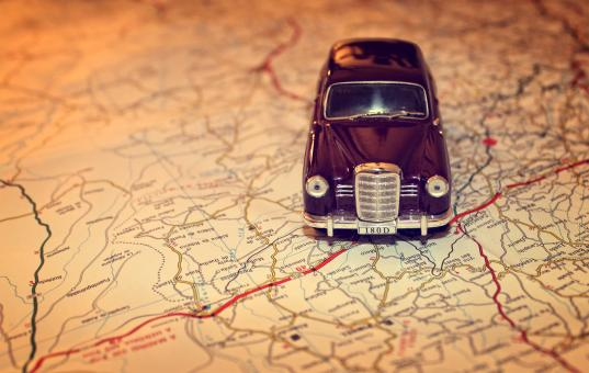 Hit the road - Travel concept with vintage miniature car on road map - Free Stock Photo