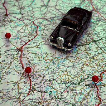 Miniature car and pushpins on a map - Travel concept - Free Stock Photo
