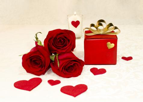 Three red roses and a gift - Free Stock Photo